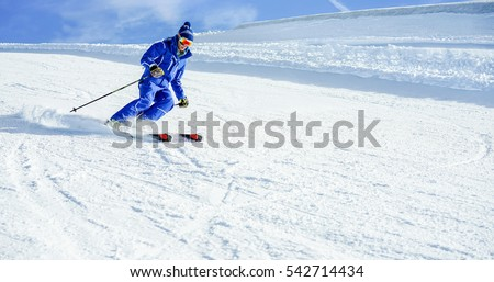 Young athlete skiing in Deux Alps french mountains on sunny day - Skier riding down for winter snow sport competition - Training and vacation concept - Warm vivid filter  #542714434