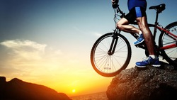Young athlete standing on a rock with bicycle
