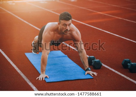 Young athlete training on running track