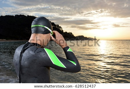 young athlete triathlon in front of a sunrise over the sea #628512437