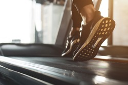 Young athlete wearing black sport shoes running on treadmill. He training for cardiovascular endurance and good health with personal trainer in fitness center.