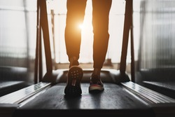 Young athlete wearing white sport shoes walking on treadmill. He training for cardiovascular endurance and good health with personal trainer in fitness center.