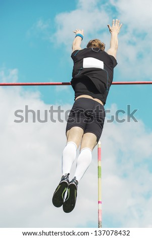 Young athletes pole vault  over the bar seems to reach the sky