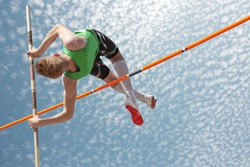 Young athletes pole vault seems to reach the sky