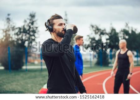 Young athletes practicing a run on athletics stadium track, having break.