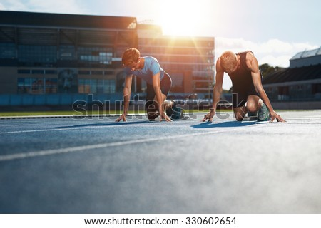 Young athletes preparing to race in start blocks in stadium. Sprinters at starting blocks ready for race with sun flare.