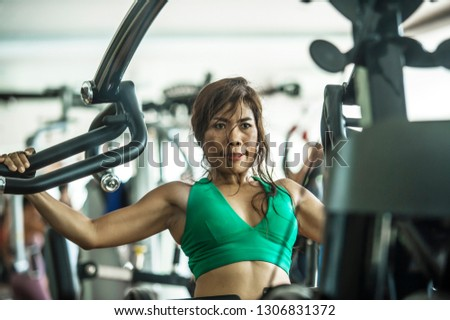 young athletic and determined Asian Indonesian woman working hard on weights using chest bodybuilding gym machine at fitness club in determination and healthy lifestyle concept #1306831372