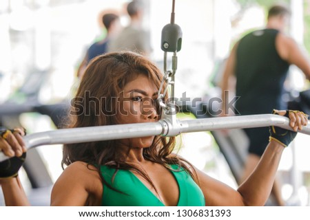 young athletic and determined Asian Indonesian woman working hard on weights using chest bodybuilding gym machine at fitness club in determination and healthy lifestyle concept #1306831393