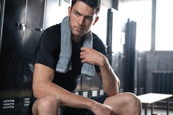 Young athletic Caucasian man sitting alone in dark gym locker room resting after workout.