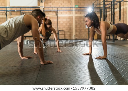 Young athletic friends doing push-ups while working out at health club
