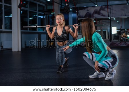 Young athletic girl lunges with a barbell in the gym under the supervision of a trainer. Female trainer teaches ward lunges with bar. Personal training. Exercises on the buttocks.