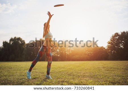 Young athletic girl playing with flying disc in the park. Professional player. Sport concept #733260841