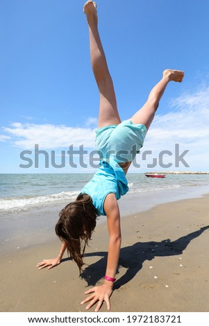 young athletic girl with her hands on the sand of the beach while performing a pirouette with her legs raised in the air Stock fotó ©