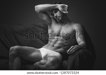 Young athletic male in underwear posing on camera.