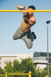 Young athletic man doing gymnastics with twirls on bars at a calisthenics gym outdoors