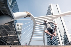 Young athletic man jumping while exercising on city bridge at the morning.