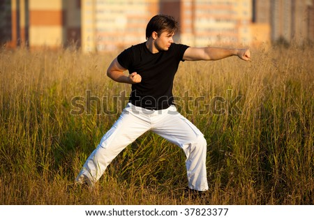 Young athletic man martial art training. Sunset red light.