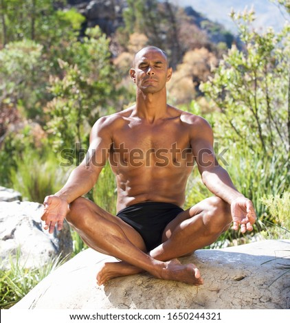 Young athletic man meditating on a rock