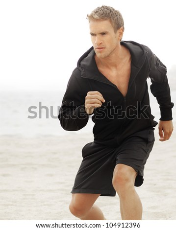 Young athletic man running with determined expression