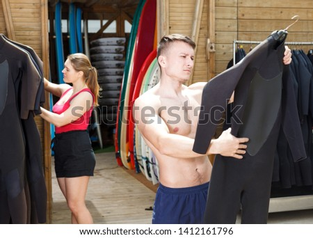 Young athletic man selecting wetsuit for surfing in surf club #1412161796