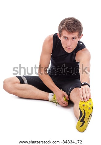 Young athletic man sitting and making stretching exercises, isolated on white background