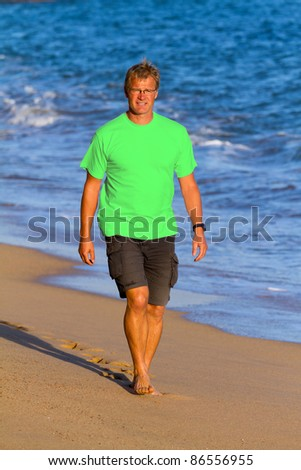 Young athletic man walks on the beach