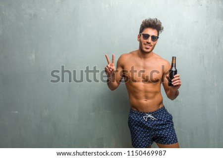 Young athletic man wearing a swimsuit against a grunge wall fun and happy, positive and natural, doing a gesture of victory, peace concept