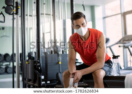 Young athletic man wearing protective face mask while having sports training in a gym during coronavirus epidemic.