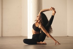 Young athletic woman doing compass yoga pose in urban loft space. Caucasian woman in her 20s practicing Parivrtta Surya Yantrasana