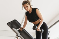 Young athletic woman doing one arm dumbbell row exercise in the gym