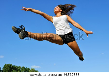 young athletic woman in a long jump on blue sky background