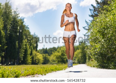 young athletic woman running on the road, exercise outdoors