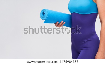 young athletic woman with a Mat for gymnastics in her hands. a fragment of a woman's body in sportswear for Pilates and yoga. weight loss with the help of training in the gym. free space, copy space