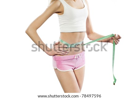 Young athletic women measuring waist. Isolated on white background