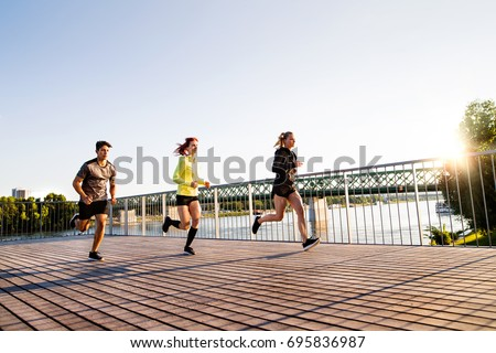 Young athtletes in the city running at the river.