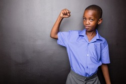 Young atractive black boy wearing school unifor looing sad and worried going to school for the first time with his one arm making flexing his muscle.