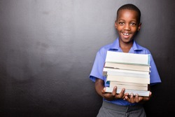 Young atractive black boy wearing school unifor while holding his school books and a green apple, looking excited about going back to school. looking excited about going back to school.