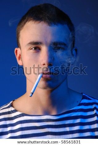 Young atractive man in striped jersey smoking