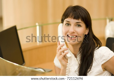 young atractive woman receptionist with phone talking to customers