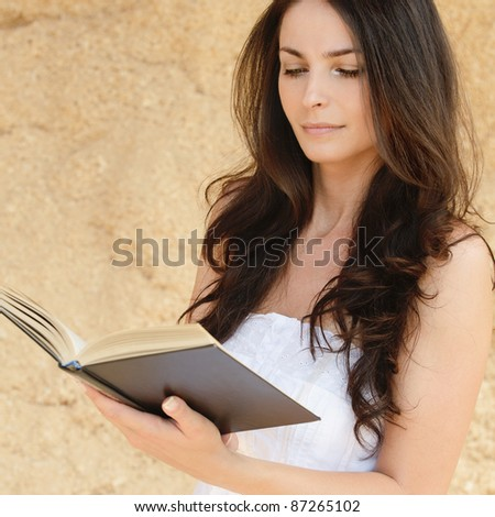 Young attarctive woman reading book against beige background.