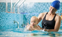 Young attentive mother is helping her little son swim in turquoise water during swimming class for infants, baby is splashing around in water. Concept of active family leisure