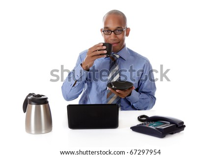 Young attractive African American businessman in office at his desk. Coffee brake time. Studio shot. White background.