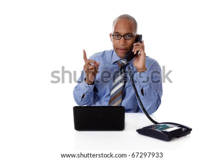 Young attractive African-American businessman in office at his desk, in front of a laptop and talking to telephone, explaining. Studio shot. White background