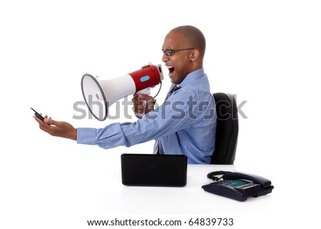 Young attractive African American businessman in office at his desk, yelling angry into megaphone at a cell phone . Studio shot. White background.