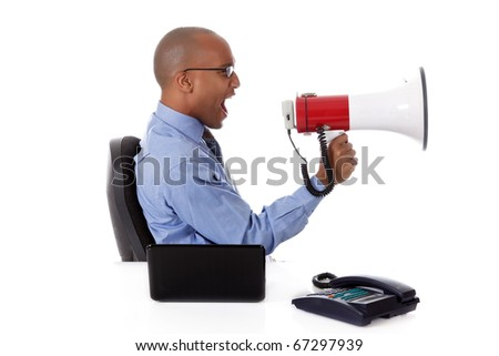 Young attractive African American businessman in office at his desk, yelling angry into megaphone. Studio shot. White background.