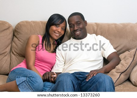 Young, attractive african american couple relaxing together on their couch. The couple are smiling at the camera. Horizontally framed shot.