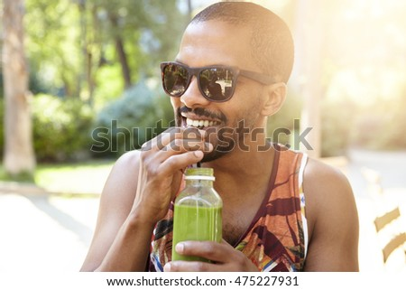Young attractive African American hipster sipping fresh green smoothie, waiting for his friends at city park on hot summer day, hiding in the shadow of big trees, wearing fashionable sunglasses #475227931