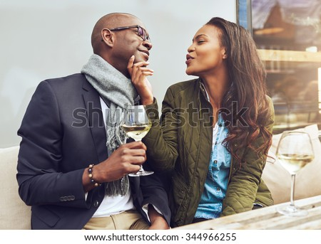 Young attractive African American woman flirting with her boyfriend puckering her lips for a kiss and caressing him on the chin