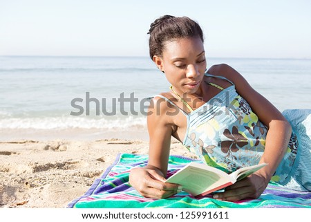 Young attractive african american woman reading a book while laying down on a beach on vacation, relaxing on the shore.