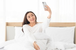 Young Attractive and Beautiful Asian women take a selfie or video call with smartphone while sitting on the bed. Happy influence Female uses mobile phone for live streaming with internet subscribers.